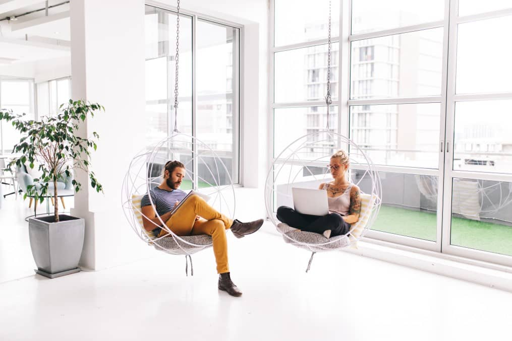 Two people working post covid in a shared office environment respecting social distancing.