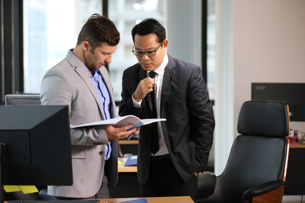 two businessmen looking at report in office coworking serviced office traditional office flexible